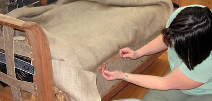sewing the lining on a small settee